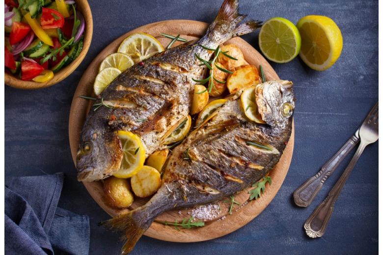 жареная рыба с картофелем и лимоном на деревянной тарелке фото