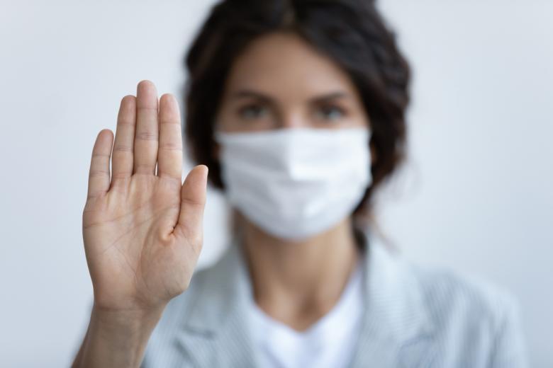женщина в маске с вытянутой вперед рукой фото