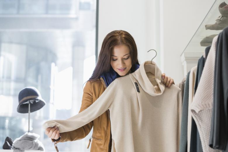 Девушка выбирает одежду в магазине фото