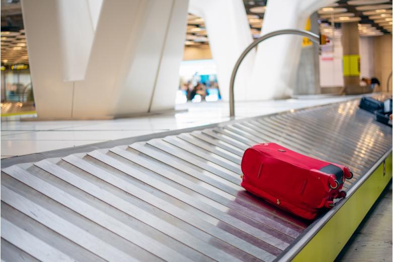 Красный чемодан забытый на ленте в аэропорте фото