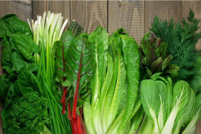 Листовые овощи на деревянном столе фото