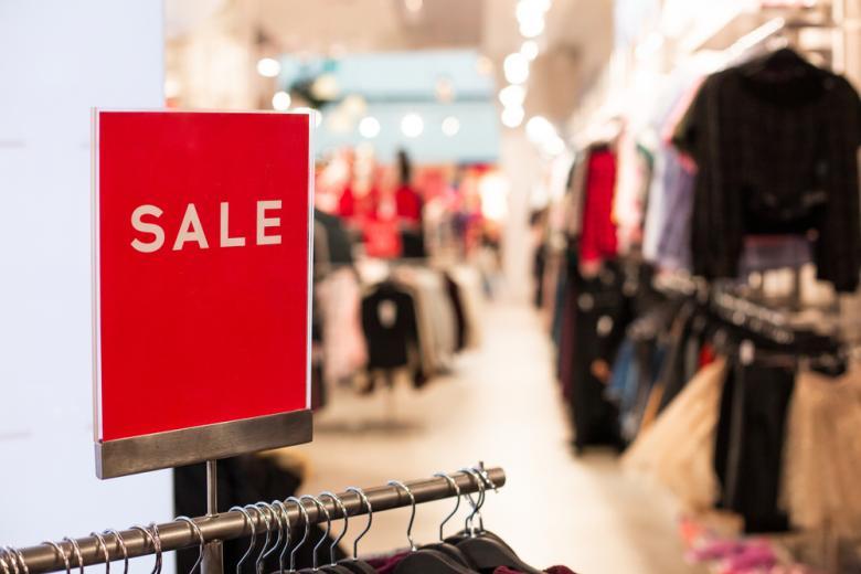 Магазин одежды с рекламой о распродаже фото