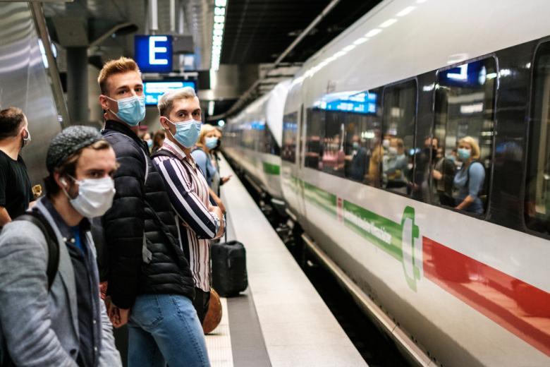 молодые люди в масках ждут поезд ICE фото