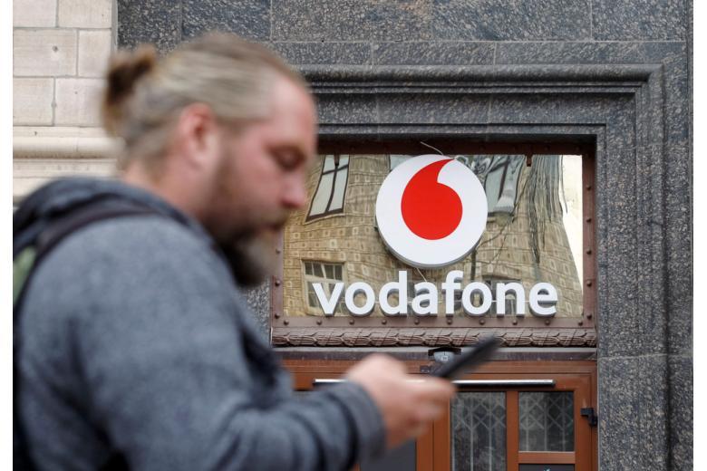 Мужчина с телефоном на фоне магазина Vodafone фото