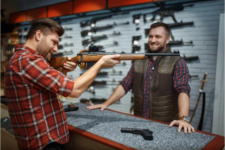 Мужчина выбирает оружие в специализированном магазине фото