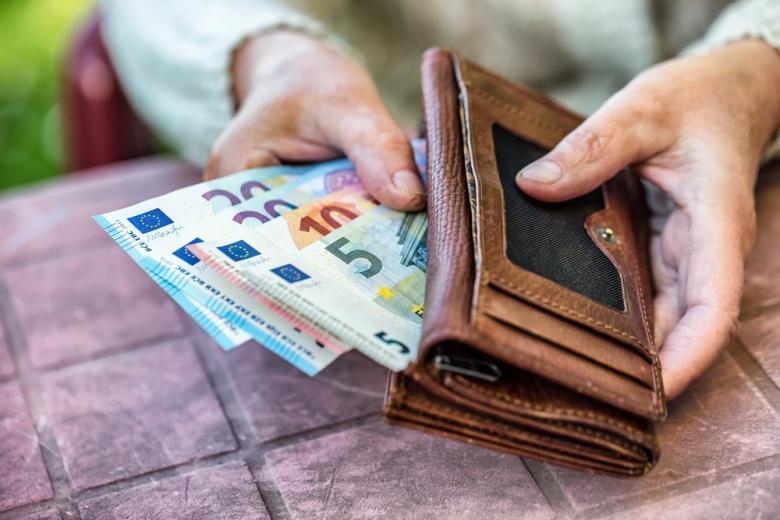 Пожилая женщина достает деньги из кошелька фото