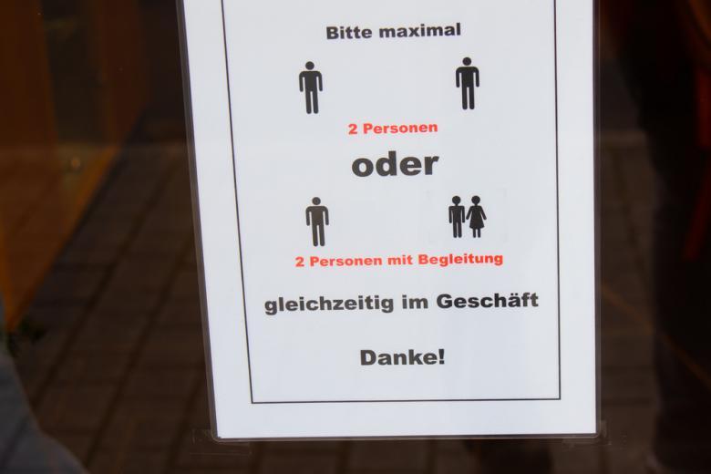 Табличка на двери магазина во Франкфурте с социальными ограничениями из-за COVID фото