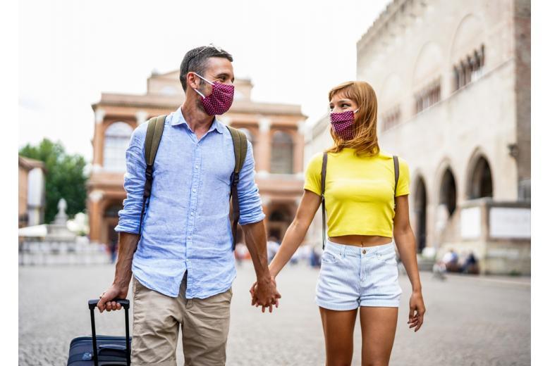туристы в масках держатся за руки фото