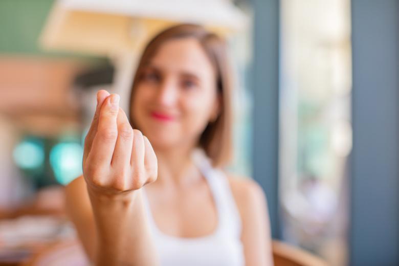 женщина жестами показывает необходимость оплаты фото