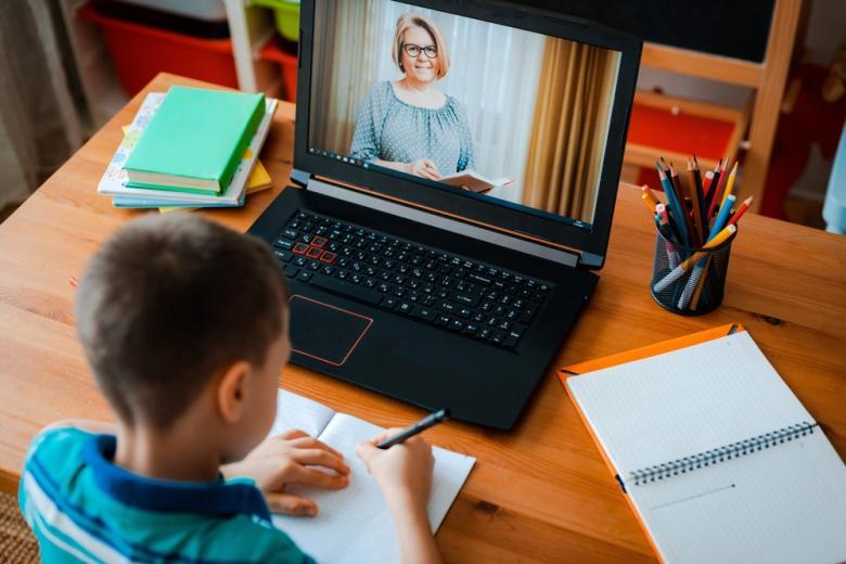 мальчик слушает учителя, ведущего видеоурок фото