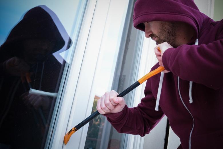 Мужчина в худи взламывает окно квартирs фото