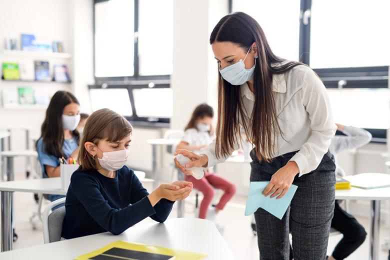 Учитель в маске брызгает ученику на руки санитайзером фото