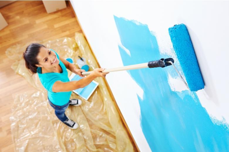 молодая женщина красит стены в квартире фото