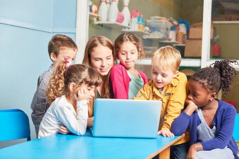 Дети и воспитательница смотрят на монитор компьютера фото