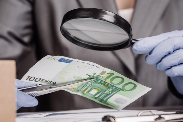 Эксперт с лупой проверяет евро на подлинность фото