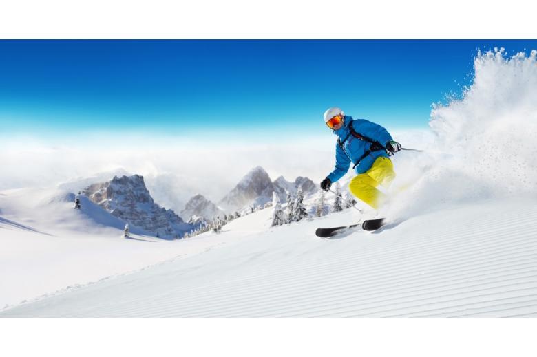 Лыжник едет вниз по альпийскому склону фото