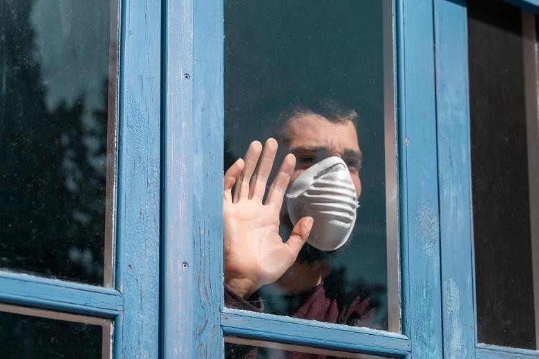 мужчина на карантине смотрит в окно фото