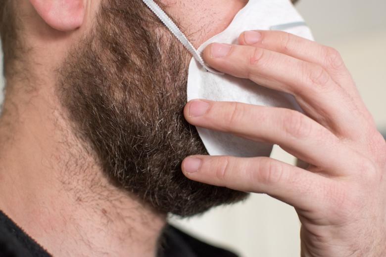 Мужчина с бородой в медицинской маске фото
