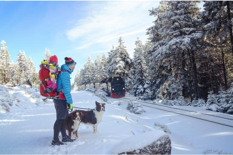 Мужчина с ребенком и собакой на заснеженном склоне горы Броккен, Германия фото