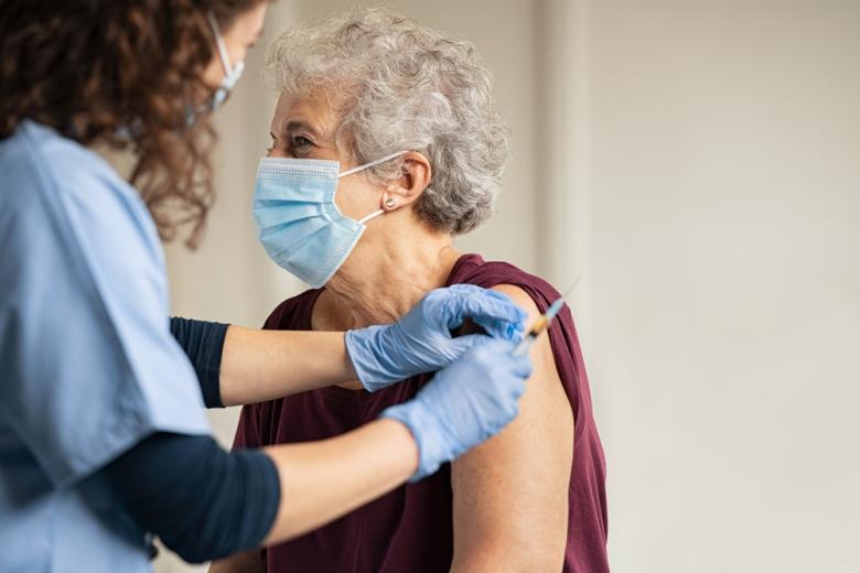 врач вводит вакцину пожилой женщине фото