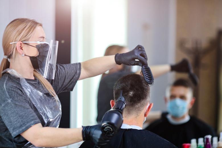 парикмахер в маске делает мужчине укладку фото