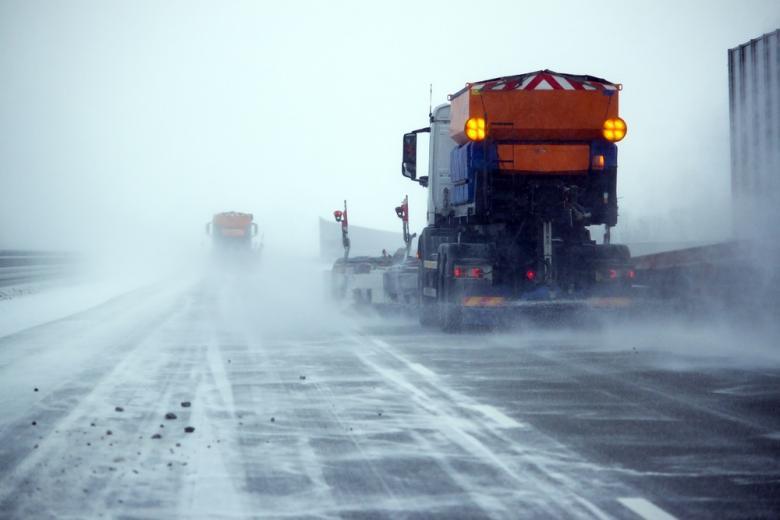 Снегоуборочные машины в метель на дороге фото