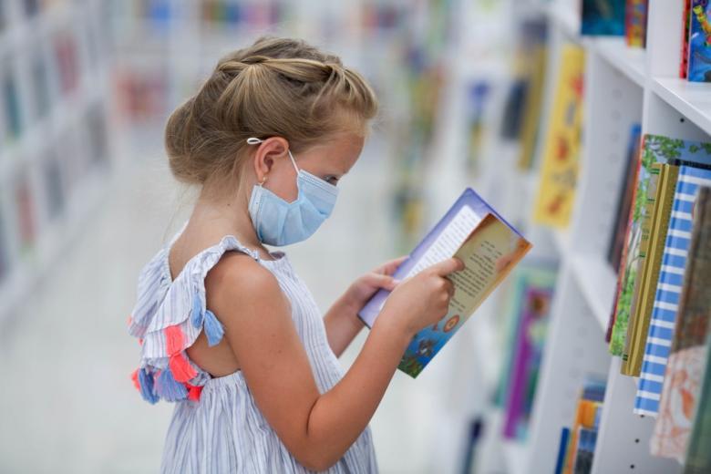 девочка в защитной маске читает книгу фото