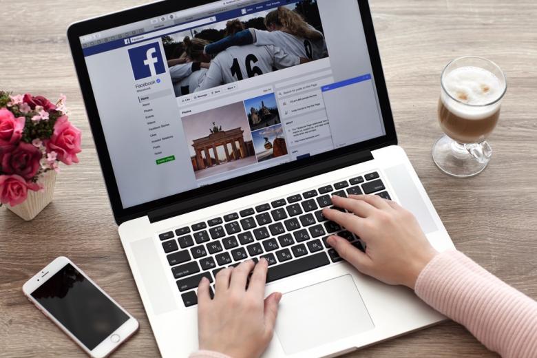 девушка просматривает ленту Facebook на ноутбуке фото