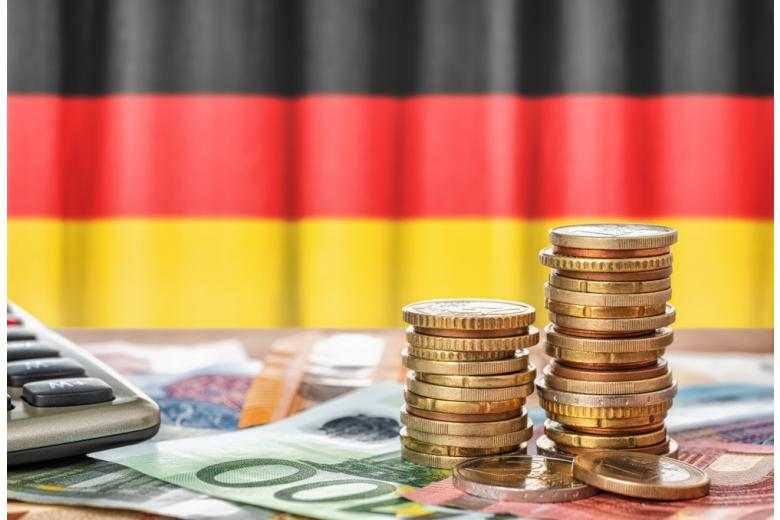 купюры и монеты евро на фоне немецкого флага фото