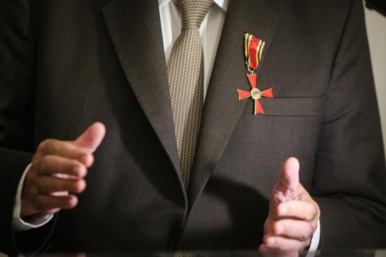 мужчина с наградой на груди и поднятыми руками фото