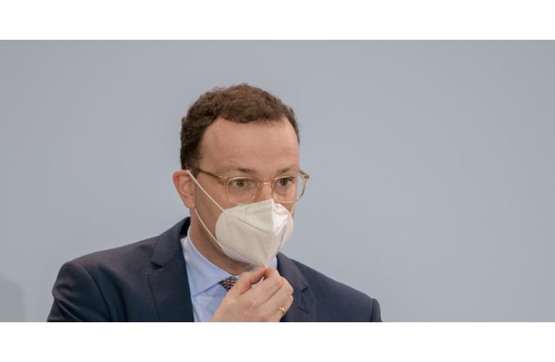 министр здравоохранения Йенс Шпан придерживает маску фото