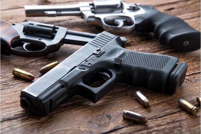 оружие разного калибра и боприпасы лежат на столе фото