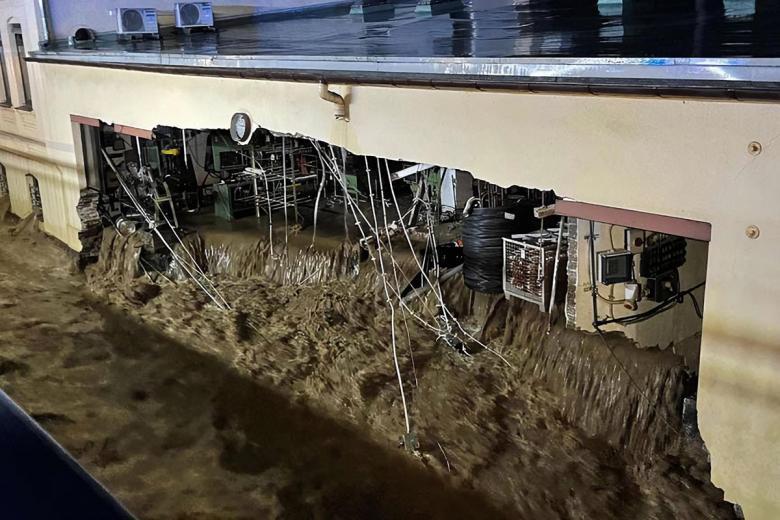 В Хагене масса воды разрушила стену дома и хлынула через здание. Фото: Alex Forstreuther / dpa