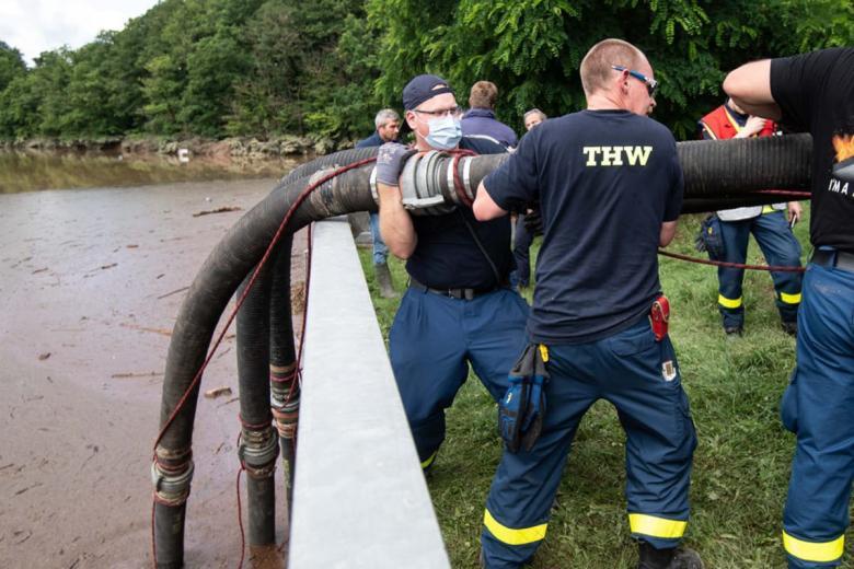 Помощники Федерального агентства по оказанию технической помощи (THW) опускают шланги в водохранилище Штайнбах для откачки воды. Фото: Marius Becker / dpa